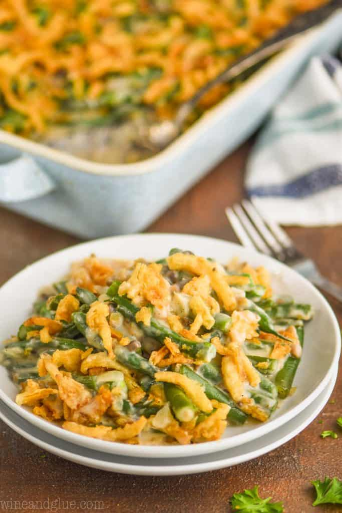 fresh green bean casserole on a small white plates with casserole in the background