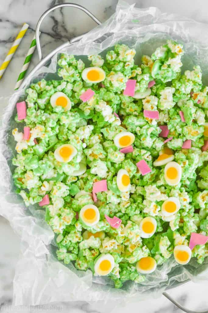 overhead view of popcorn coated in green chocolate in a large metal tray with candy eggs and candy ham to make green eggs and ham popcorn