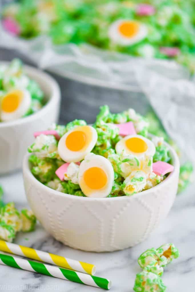 small white bowl filled with white chocolate popcorn that has been colored green and added candy eggs and pink taffy pieces to make green eggs and ham popcorn