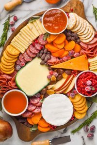 overhead view of an oval wood board with four varieties of cheese cut and whole, sliced pears, three small bowls of spreads, pear slices, persimmon slices, and hard meats