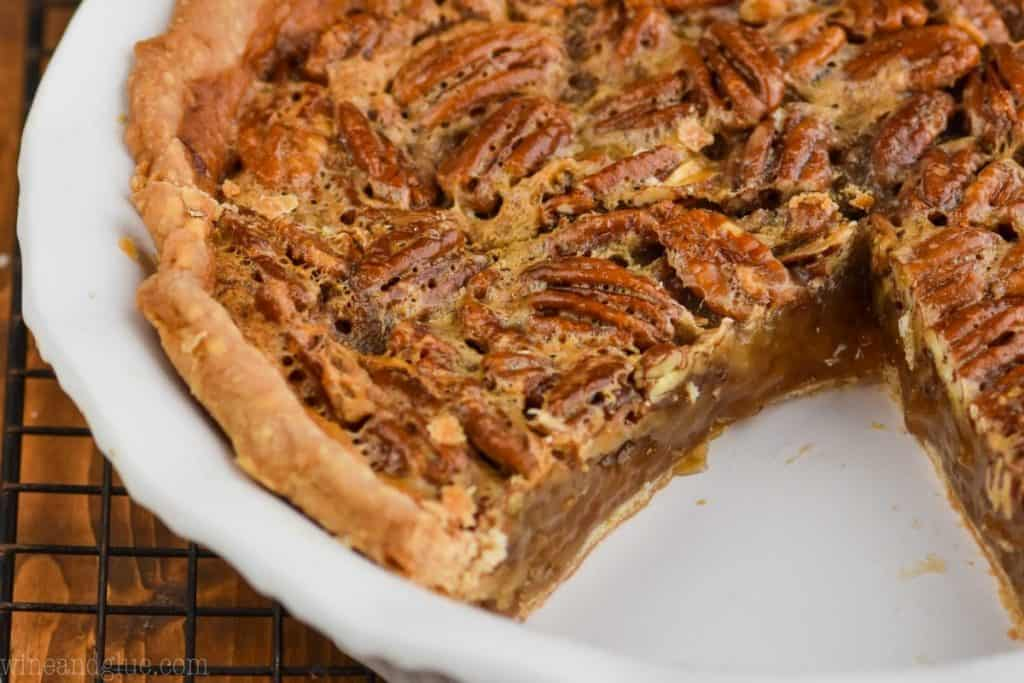 landscape view of a cut into pecan pie, you can see its caramel looking insides