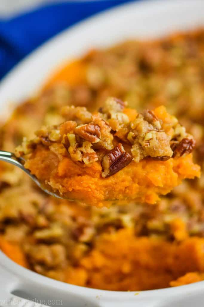 a close up of a spoonful of sweet potato casserole topped with pecans