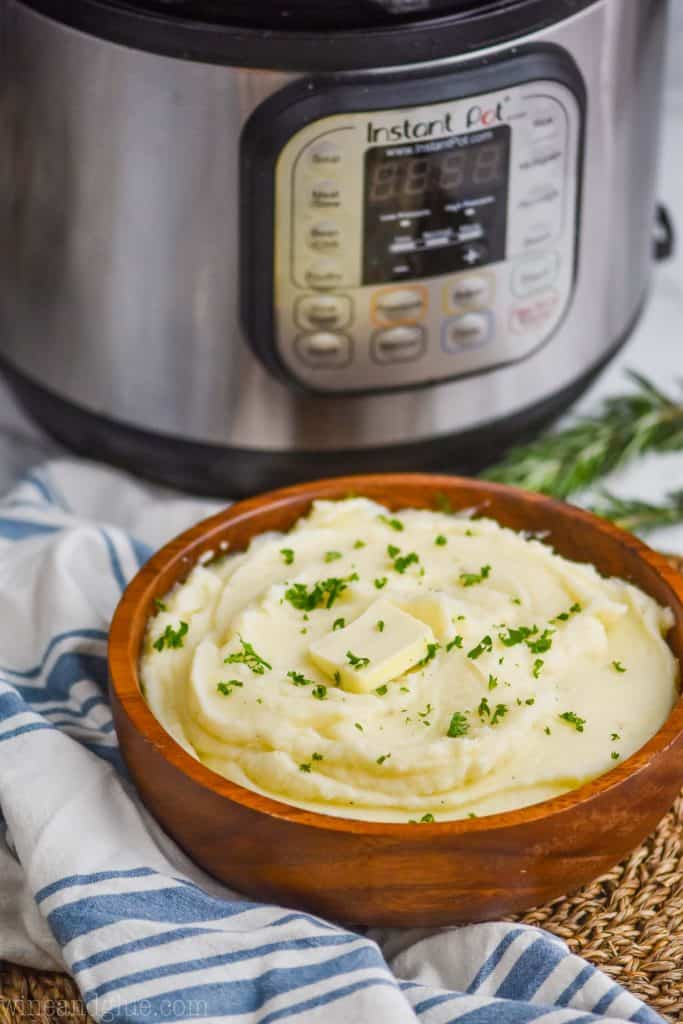 mashed potatoes made in the instant pot in a wooden bowl sitting in front of an instant pot, with a cloth napkin next to it