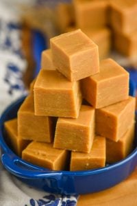 a pyramid of peanut butter fudge piled into a small blue dish with handles on a white napkin and a wood block