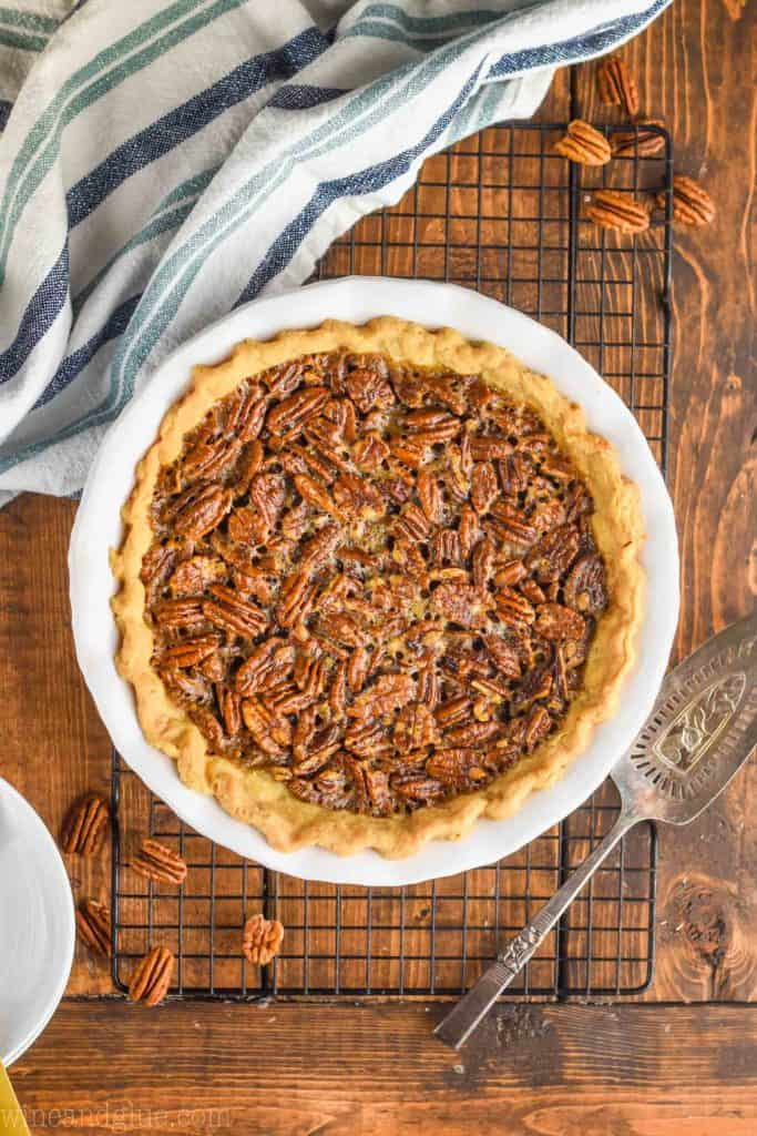 pulled back overhead view of the best pecan pie recipe in a white ceramic pie plate on a wire rack with an antique pie server next to it