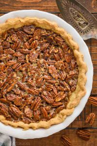 overhead view of a full pecan pie recipe in a white ceramic pie plate with an antique pie server next to it and sitting on a wire rack