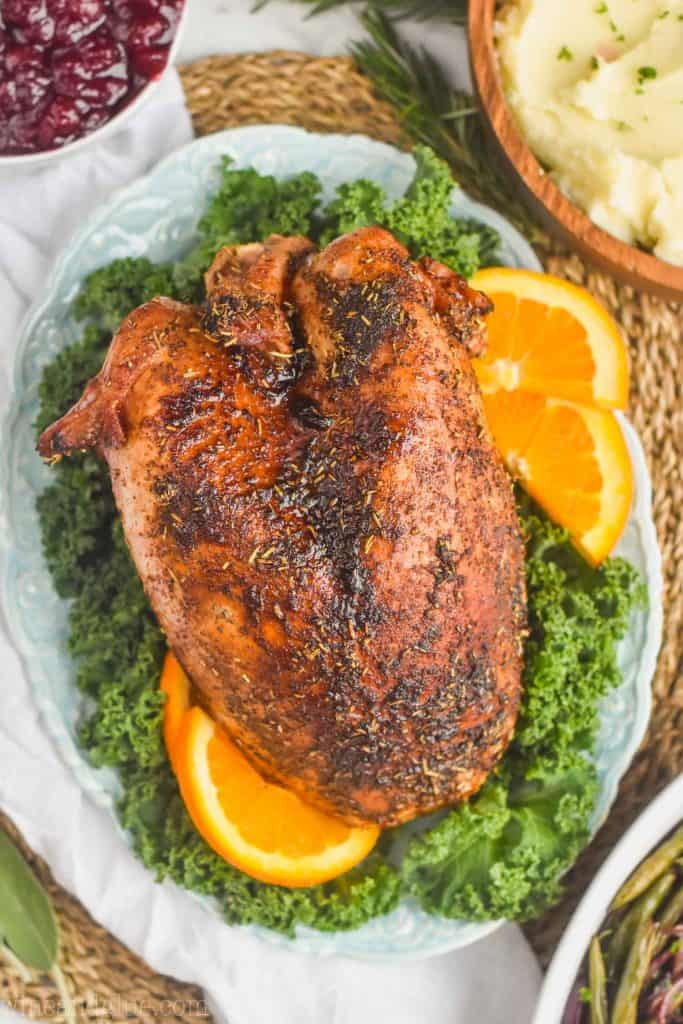 overhead view of a roast turkey breast sitting on a bed of greens with orange slices around it