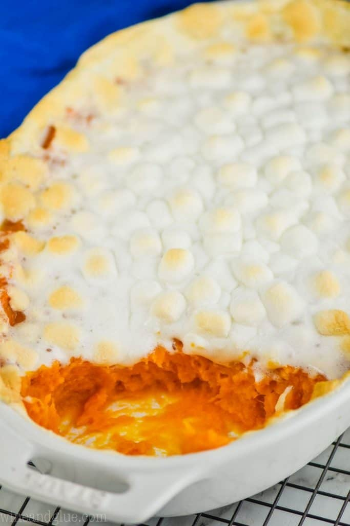 white casserole dish from the side with sweet potato casserole topped with marshmallow that has been scooped out