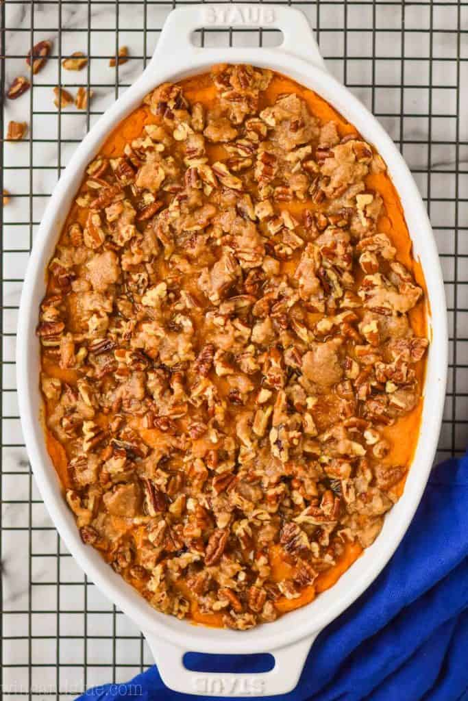 overhead view of a sweet potato casserole recipe topped with pecans and brown sugar in a white oval casserole dish