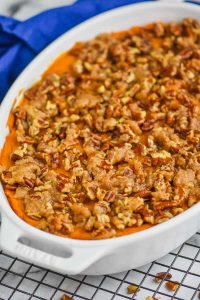 sweet potato casserole with pecans in a white casserole dish on a wire rack with a blue towel in the background