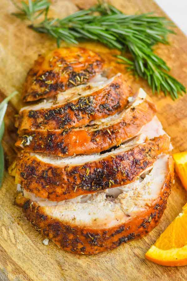 turkey breast that has been cooked and is cut up sitting on a cutting board with orange slices and rosemary sprigs