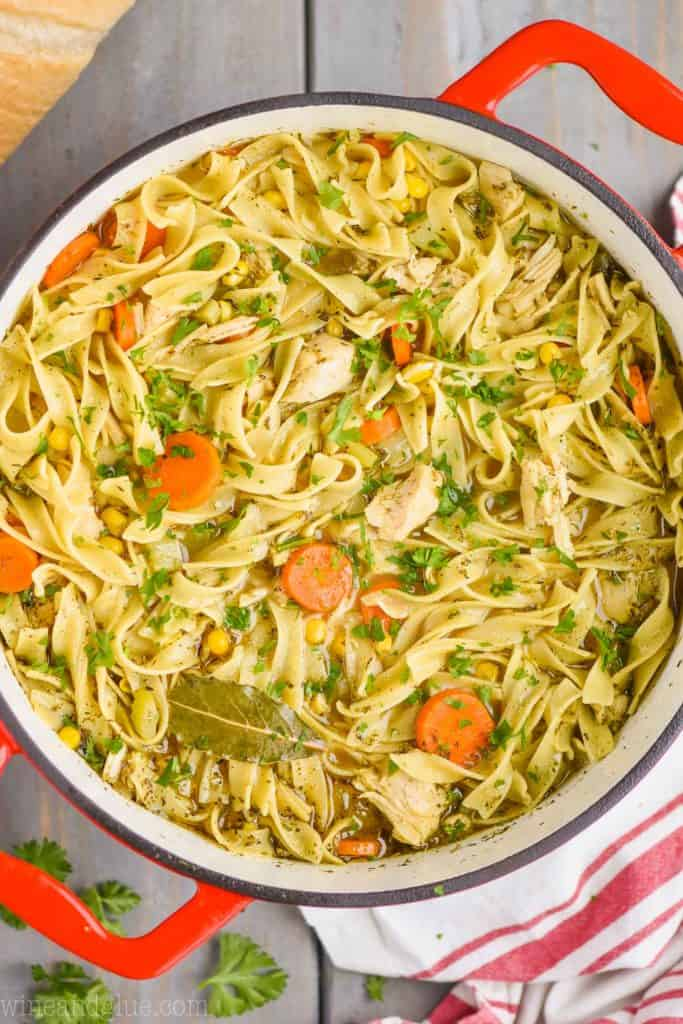 overhead view of a red handled stock pot full of turkey noodle soup - long noodles, pieces of turkey, a bay leaf, carrots, and corn are visible