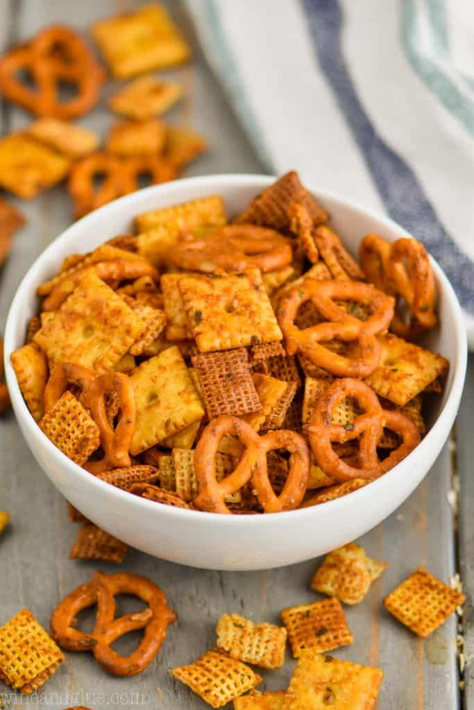 small white bowl full of homemade chex mix recipe on a gray board with a white napkin in the background