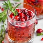 tumbler with christmas sangria in it, garnished with fresh cranberries and a sprig of rosemary
