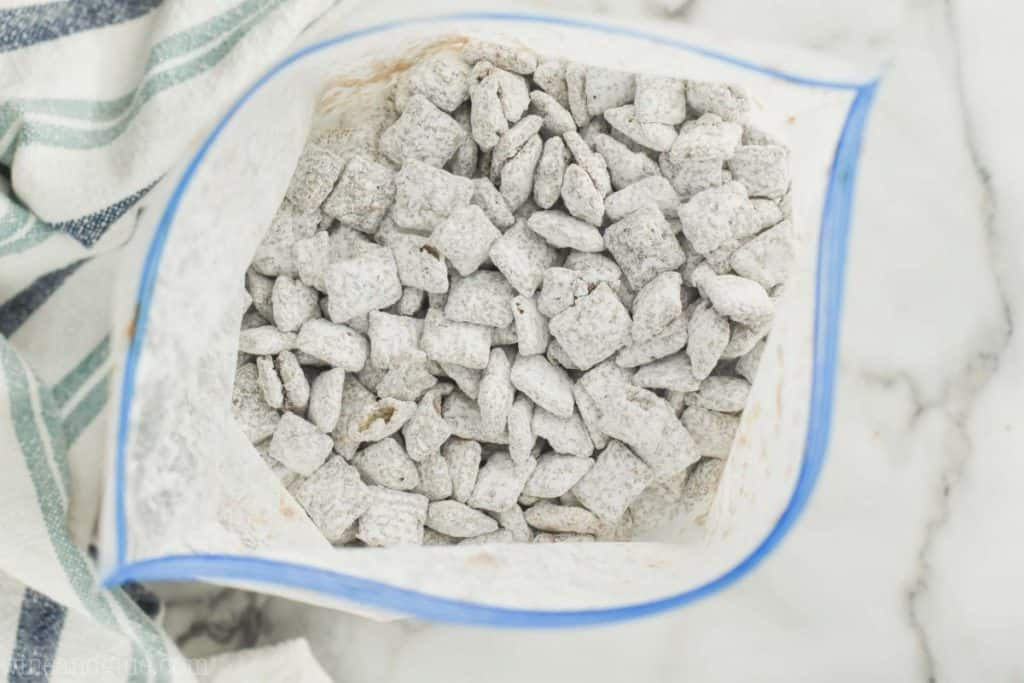 overhead view of muddy buddies in a plastic zip locked bag after they have been tossed with powdered sugar