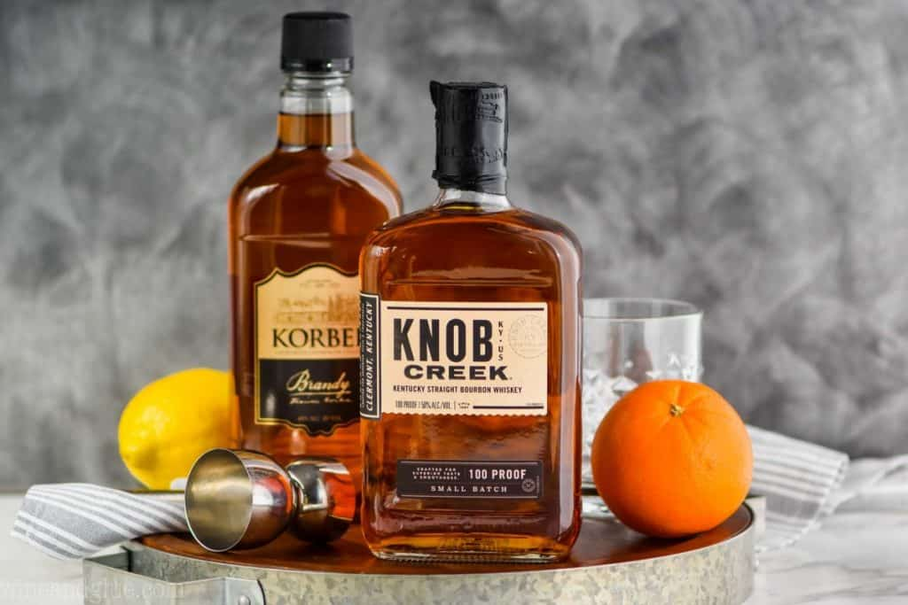 a small wood tray containing a bottle of bourbon whiskey, a bottle of brandy, a double jigger, a small glass tumbler, an orange, and a lemon