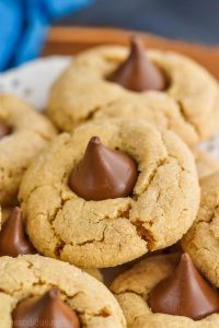 a close up photo of a peanut butter blossom - crisp peanut butter cookie with a Hershey kiss buried into the top