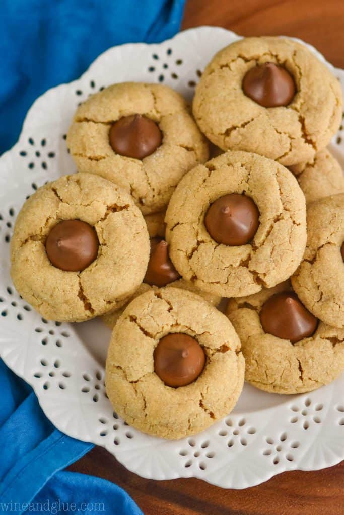 overhead view of peanut butter Hersey kiss cookies on a white detailed plate with a blue napkin and on a wood board