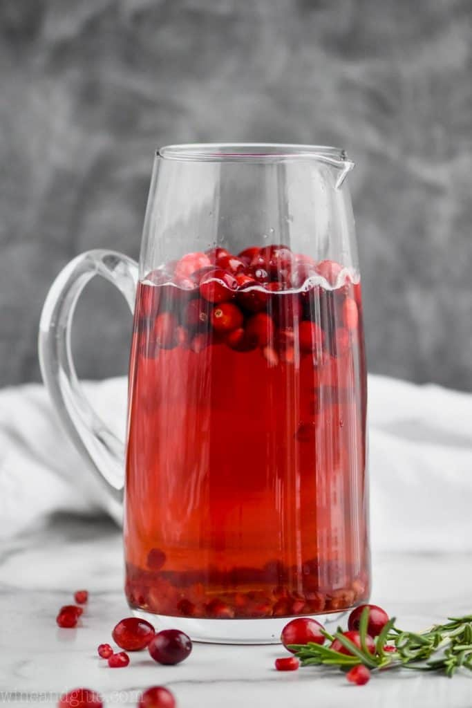a tall pitcher filled with red holiday sangria with floating cranberries in it against a gray background