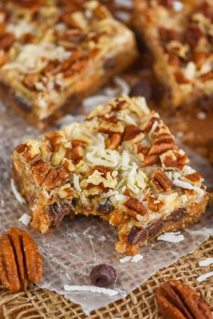 up close overhead picture of a seven layer bar on a piece of parchment paper with a bite missing, coconut shreds and pecan pieces visible on the top of the gooey bar