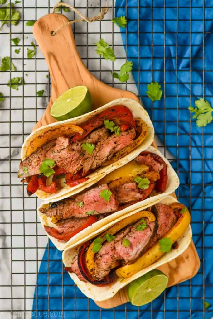 overhead view of three steak fajitas on a small wood cutting board on a wire rack, garnished with fresh cilantro