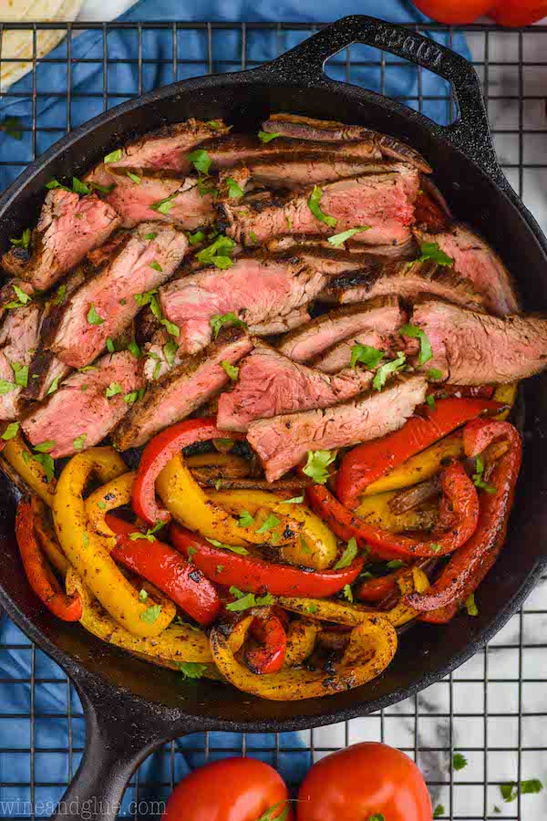 close up of cooked steak sliced thin with sliced peppers in a cast iron skillet, seasoned with fajita marinade