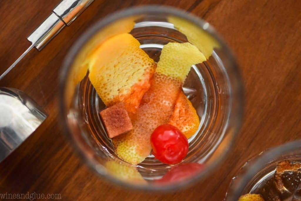 an overhead close up view of the bottom of a tumbler glass with a lemon peel, orange peel, maraschino cherry, and sugar cube soaked with brown bitters