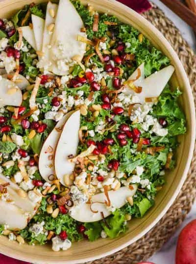 overhead view of a bowl of kale, pomegranate seeds, blue cheese, pine nuts, and pear slices for a winter kale salad