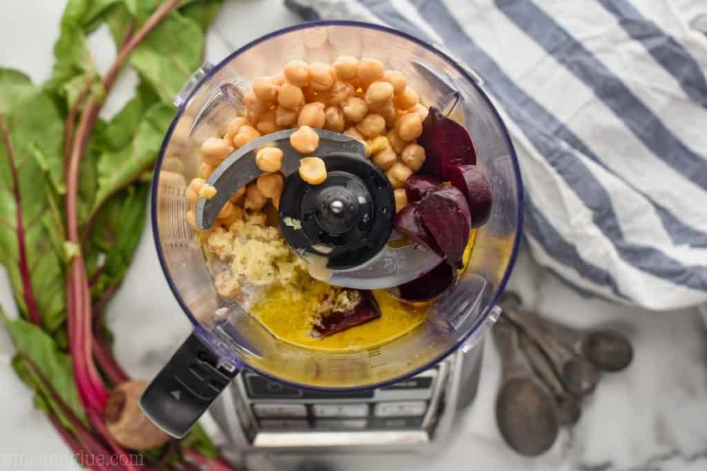 overhead view of a food processor with roasted beets, chick peas, garlic, tahini, lemon juice, and olive oil