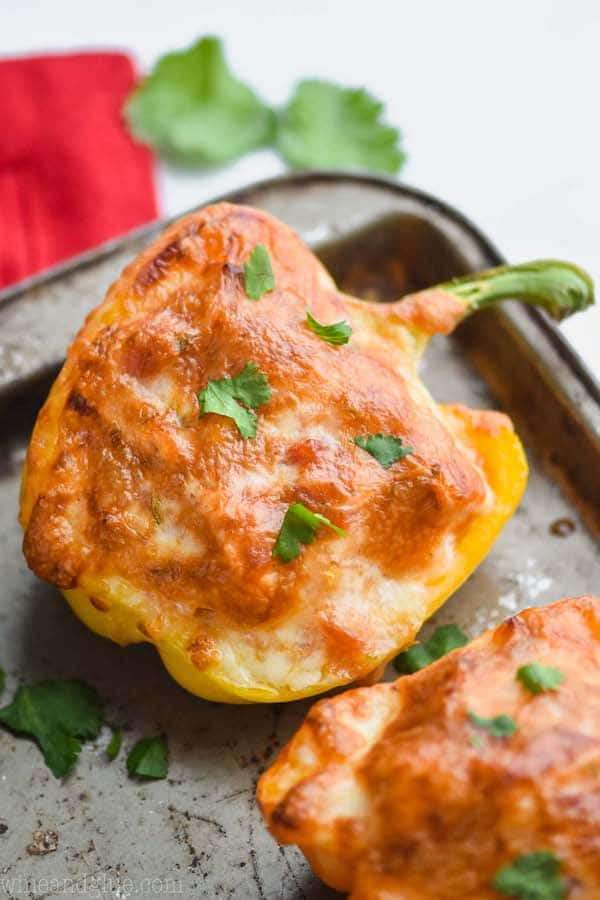 a half yellow bell pepper that is a chicken fajita stuffed pepper topped with bubbly brown cheese on an old baking sheet and garnished with cilantro