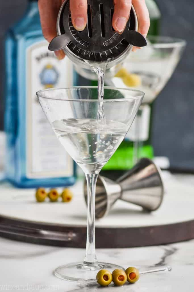 straining a gin martini into a martini glass with a bottle of Bombay sapphire on a tray in the background and a metal jigger on the tray