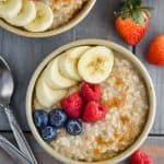 overhead view of two small bowls of instant pot steel cut oats with berries, banana slices, and brown sugar on a blue wood board