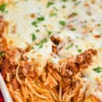 a close up of a white ceramic baking dish full of baked spaghetti topped with cheese and fresh parsley