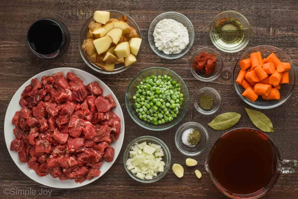 overhead view of small plates and bowls holding all of the ingredients for beef stew