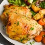 close up of baked chicken thighs on a plate with lettuce and roasted root vegetables