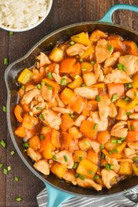 close up overhead overhead Hawaiian chicken recipe in a skillet garnished with green onions