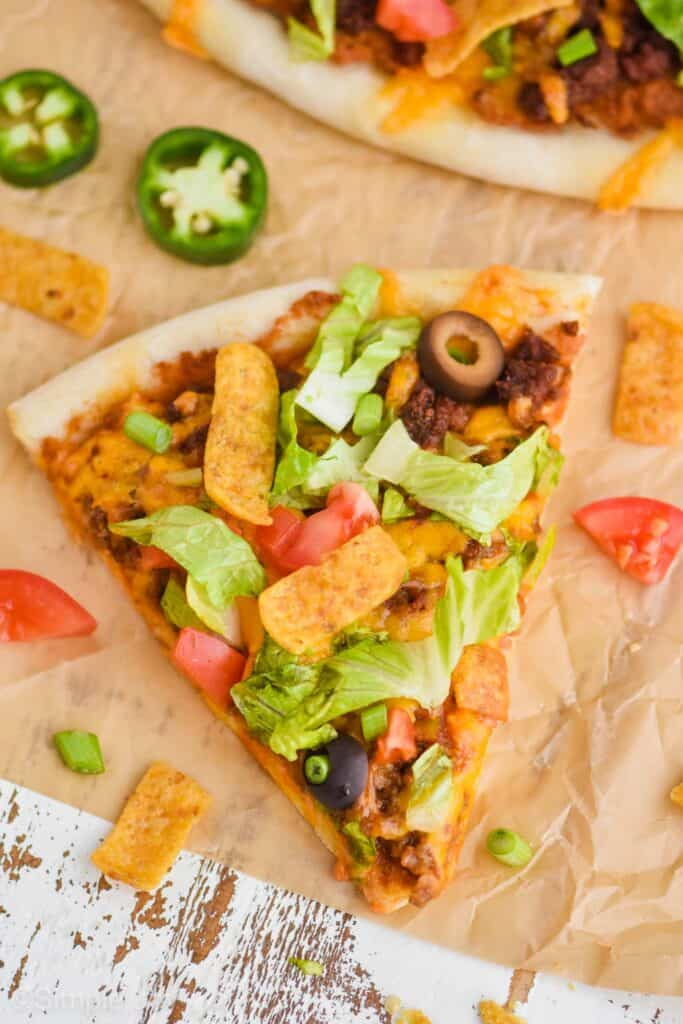 once slice of taco pizza on brown parchment paper