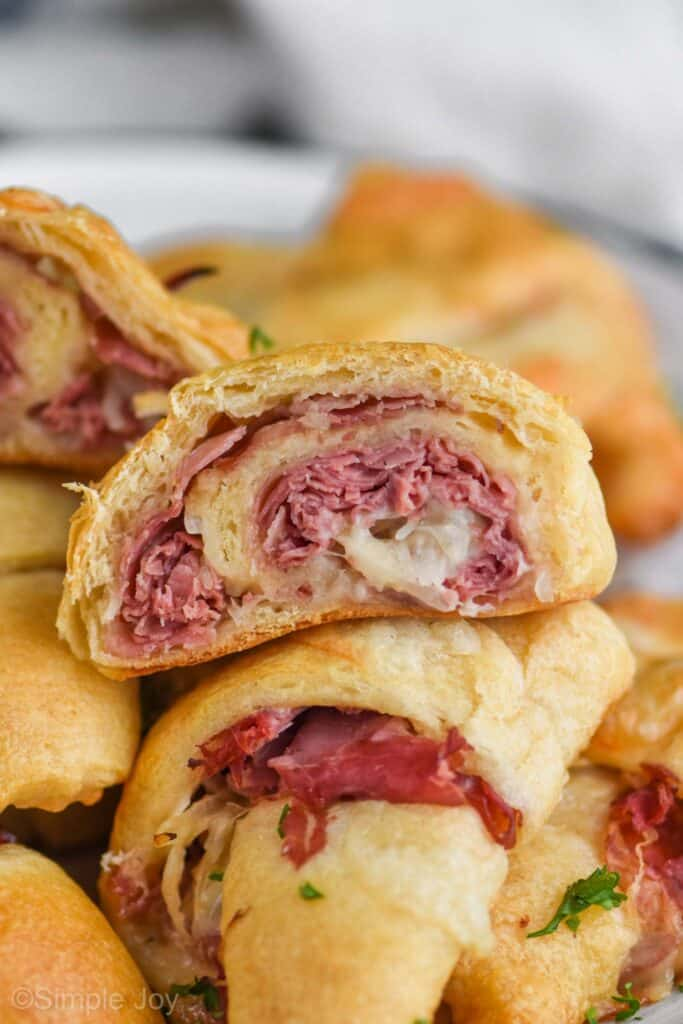 close up of a reuben crescent roll cut in half, you can see corned beef and melted Swiss cheese