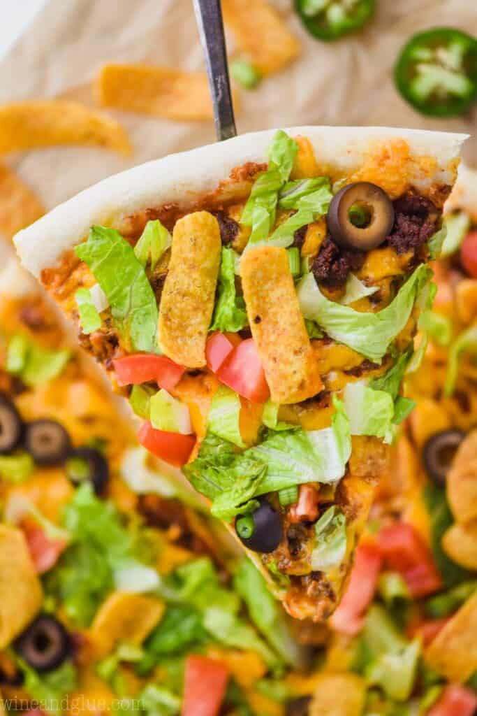 a slice of taco pizza that is being held up high over the rest of the pizza