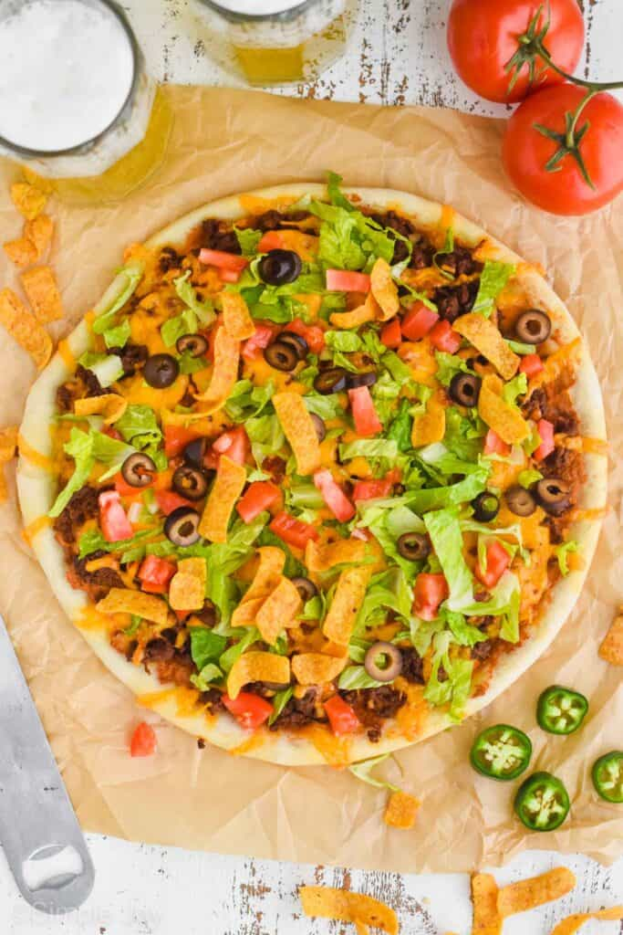 overhead view of a whole taco pizza with jalapeños and chips and beer around it