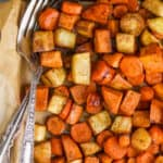 overhead view of a parchment lined baking sheet full of roasted root vegetables with a fork and spoon in the pan