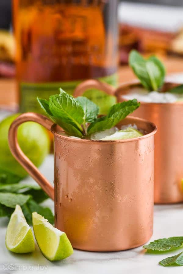 a copper mug filled with ice for a Kentucky mule, garnished with mint leaves, two lime wedges next to it
