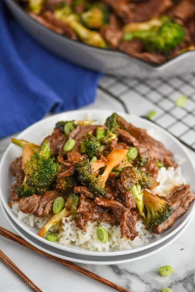 overhead photo of two white plates with white rice and beef and broccoli stir fry with a wire cooling rack in the background and a cloth blue napkin