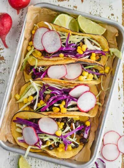 overhead of four vegan black bean tacos on a rimmed baking tray, garnished with sliced radishes, shredded cabbage, and corn