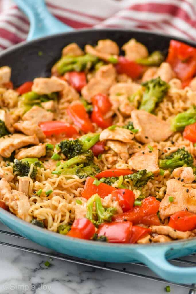 close up side view of a teal skillet holding ramen noodles, chicken, broccoli, and red pepper for stir fry dinner