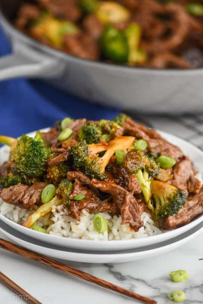 two small white plates stack with white rice and easy beef and broccoli on top of it, the rest of the skillet in the background