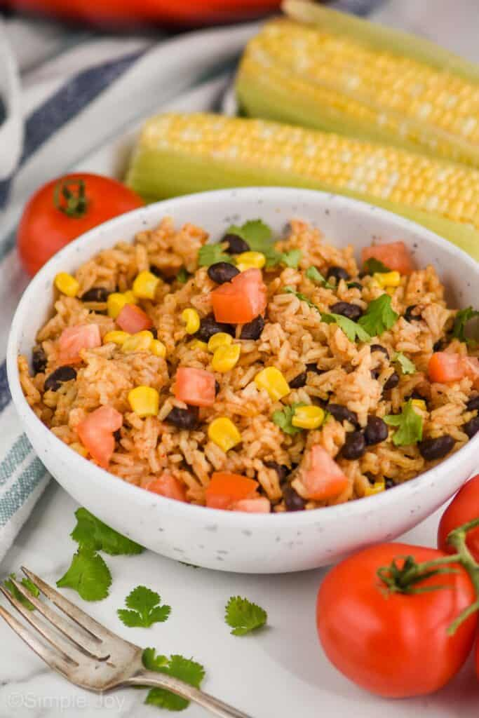 side view of a speckled white bowl with easy black beans and rice recipe with corn, tomatoes, and cilantro, fresh corn and tomatoes in the background