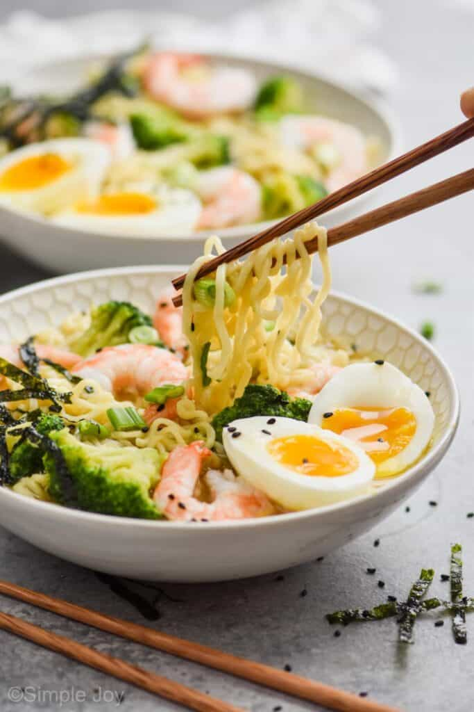 chopsticks lifting ramen noodles out of a bowl that also has broccoli, shrimp, and a soft boiled egg