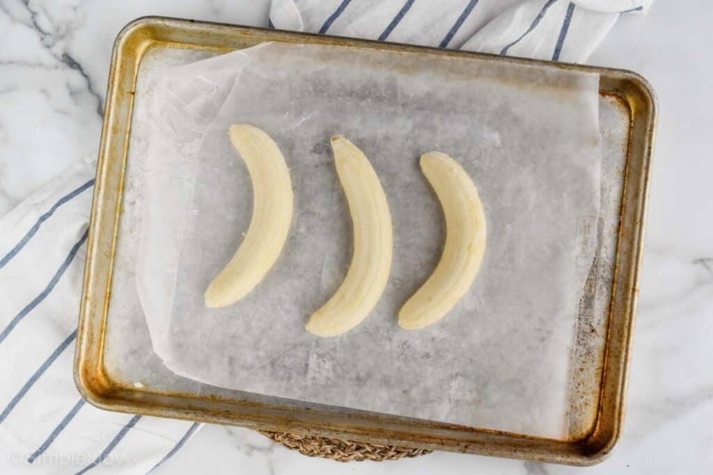 overhead view of three bananas that have been peeled and are sitting on a wax paper lined baking sheet to be frozen