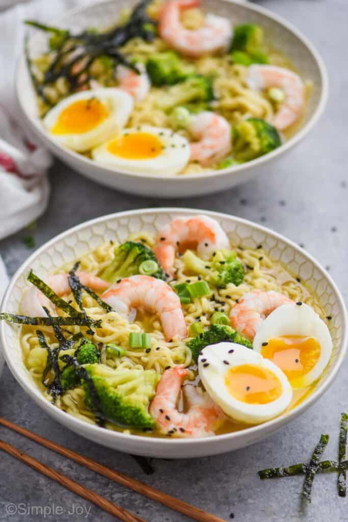 side view of a two bowls of simple homemade ramen with shrimp, broccoli, seaweed, and a soft boiled egg